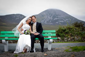 Newly married couple relax on a bench at the foot of Croagh Patrick, Co. Mayo