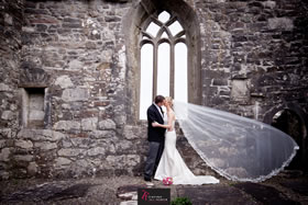 Bride and groom embrace in old stone church